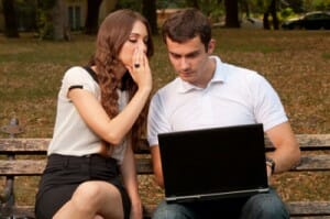 woman-whispering-to-man-with-a-laptop-image-from-shutterstock