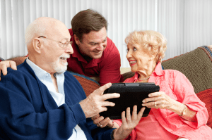 Image of senior couple being helped by a tech coach, from Shutterstock