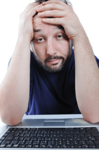 man-at-laptop-holding-head-image-from-shutterstock