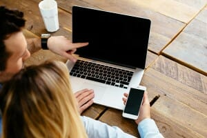 couple-comparing-laptop-and-smartphone-image-from-shutterstock
