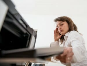 woman-frustrated-looking-at-printer-image-from-shutterstock